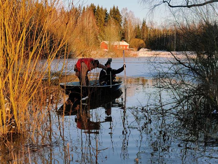 kaksi miestä veneessä vesi osin jäätynyt