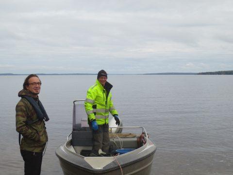 Mies seisoo rannassa veneen vierellä. Toinen mies seisoo veneessä, taustallaan järvenselkä.