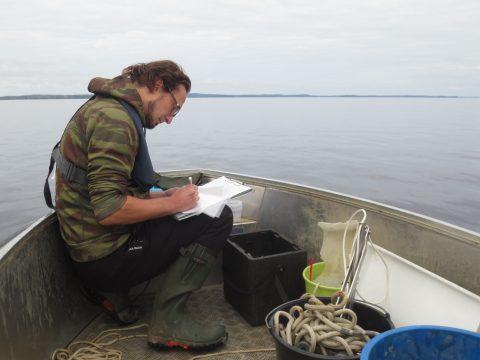 Mies istuu veneessä ja kirjoittaa.