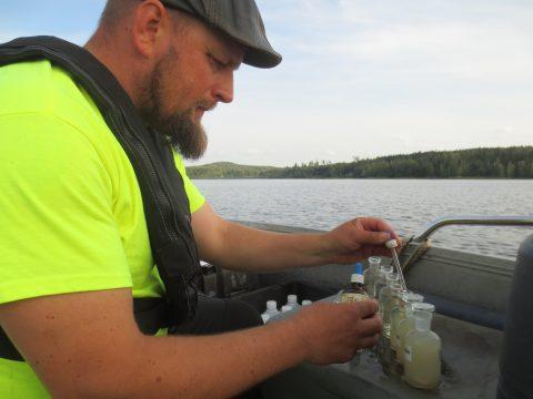 Mies laittaa vesipulloihin pipetillä reagenssia.