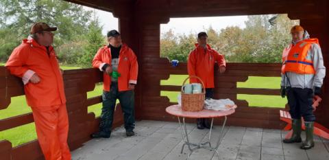 Neljä oranssivaatteista miestä seisoo ulkona katoksessa pienen pöydän ympärillä